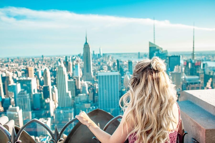 Books about destinations. Blonde woman overlooking New York City skyline.